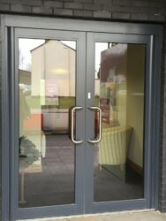 These doors are a main entrance to a recently built retirement village but are in the same colour with contrasting handles.